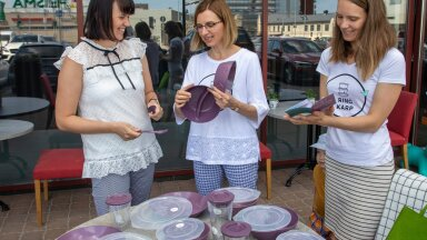 Kadrin Pintson ja Katarina Papp näitavad restorani Brasserie11 juhataja Kati Plaamusele (vasakul) RingKarbi taaskasutatavaid toidunõusid.
