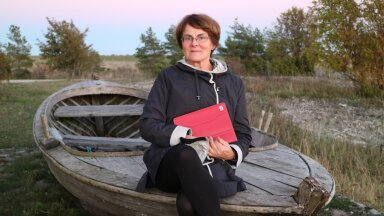 Liia Hänni istub Saaremaal Roopa lahe ääres vanas kaluripaadis, käes omaaegne lahutamatu punane iPad.