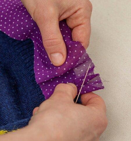 Lõigake õhukesest kangast 5 cm laiused pikad ribad ning hakake neid sättima kampsuni serva.